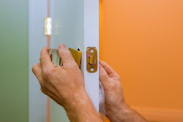 Trabalhador manual reparar a fechadura da porta nas mãos do trabalhador, instalando o novo cacifo da porta
