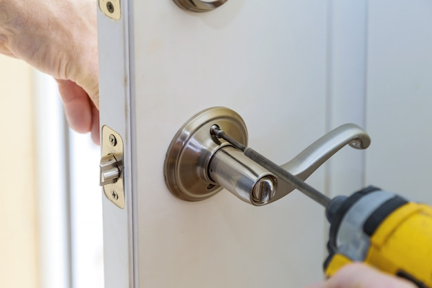 Trabalhador manual reparar a fechadura da porta nas mãos do trabalhador instalar nova porta do armário