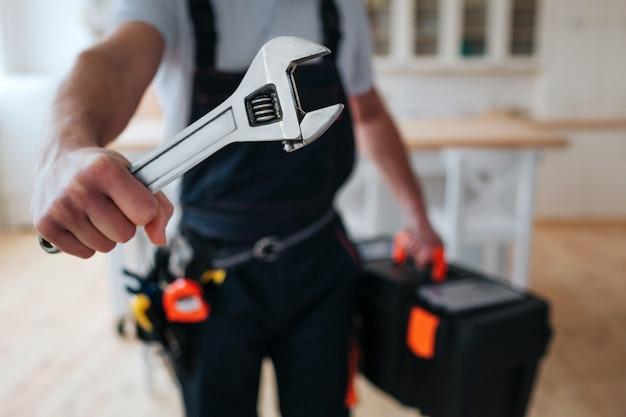 Trabalhador manual segurando a caixa de ferramentas e chave nas mãos perto da câmera
