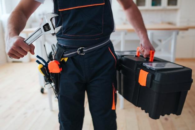 Trabalhador manual segurando a caixa de ferramentas e chave nas mãos