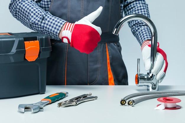 Trabalhador manual segurando a torneira e aparecendo o polegar. encanador.