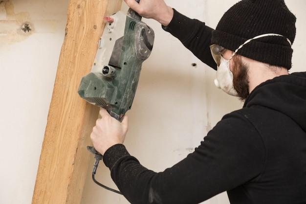 Trabalhador manual trabalha com lixadeira de detalhes, reformando uma casa