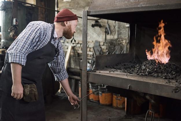 Trabalhador manual usando carvão para queimar o fogo na fornalha durante seu trabalho na fábrica