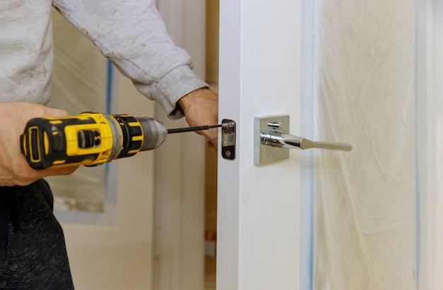 Trabalhador manual usando uma broca para instalar a fechadura na porta de uma casa