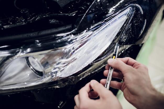 Trabalhador mãos instala carro pintura proteção filme envoltório farol auto