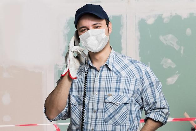 Trabalhador mascarado falando ao telefone, conceito de trabalho covid ou de pandemia de coronavírus