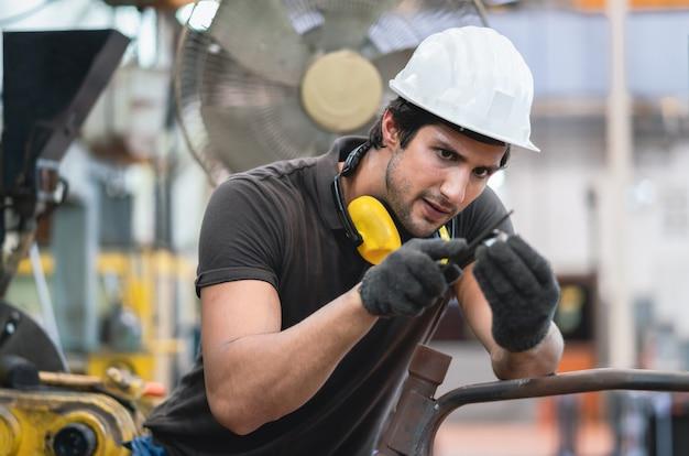Trabalhador masculino ajustar parte do equipamento da máquina na linha de produção na fábrica