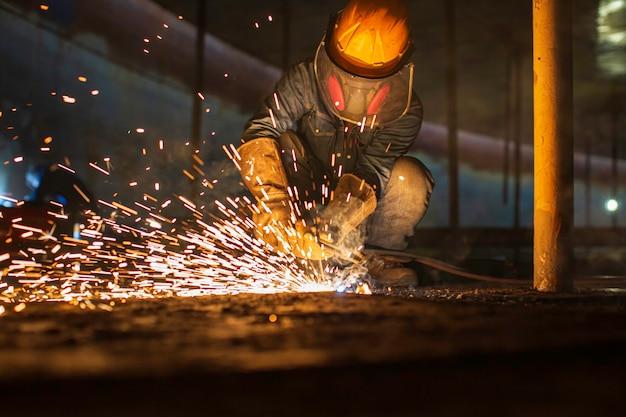 Trabalhador masculino corte de metal faísca na placa de aço do fundo do tanque com flash de luz de corte de perto, use luvas de proteção e máscara em espaço confinado lateral.