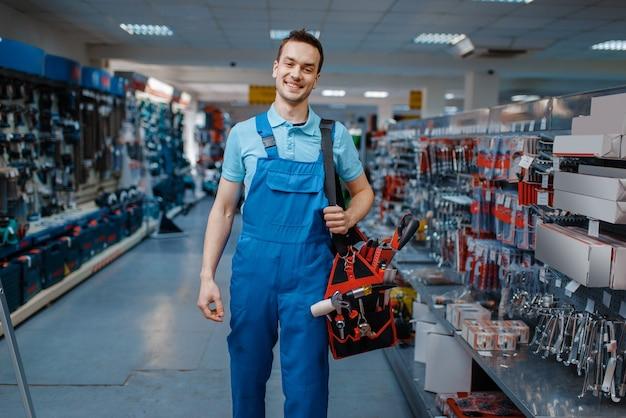 Trabalhador masculino de uniforme detém a caixa de ferramentas na loja de ferramentas. escolha de equipamento profissional na loja de ferragens