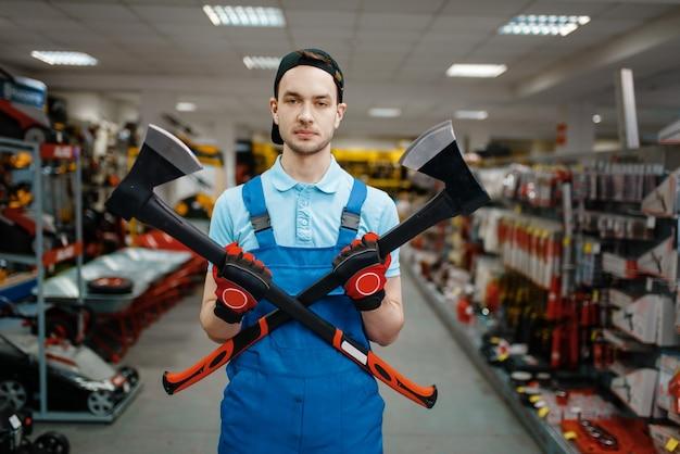 Trabalhador masculino de uniforme detém dois machados na loja de ferramentas. escolha de equipamento profissional em loja de ferragens, supermercado de instrumentos