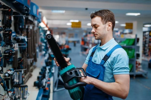 Trabalhador masculino de uniforme detém serra elétrica na loja de ferramentas.