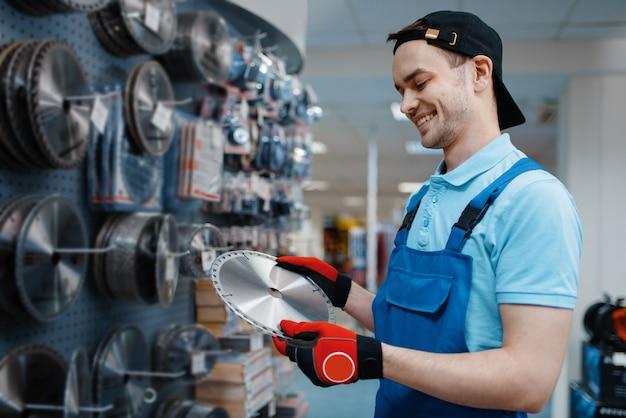 Trabalhador masculino de uniforme, escolhendo o disco afiado para serra na loja de ferramentas. escolha de equipamento profissional em loja de ferragens, supermercado de instrumentos