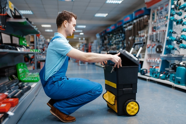 Trabalhador masculino de uniforme segura caixa de ferramentas sobre rodas na loja de ferramentas