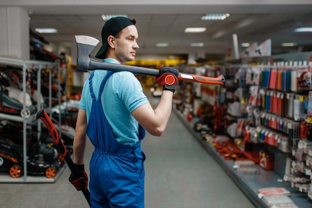 Trabalhador masculino de uniforme segura dois machados, loja de ferramentas
