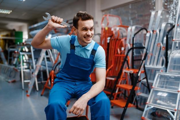 Trabalhador masculino de uniforme sorridente segurando a chave inglesa na loja de ferramentas
