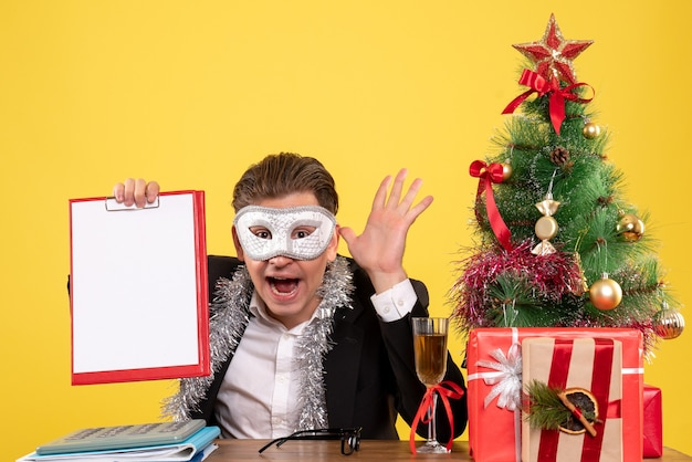 Trabalhador masculino de vista frontal usando máscara de festa e segurando uma nota de arquivo