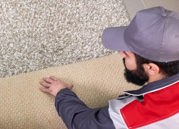 Trabalhador masculino, desenrolando o tapete no chão em casa, vista de cima
