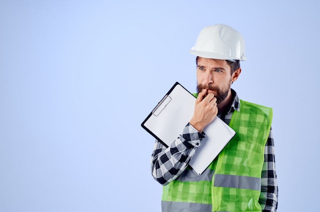 Trabalhador masculino em um capacete branco projeta fundo azul profissional