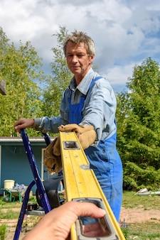 Trabalhador masculino em um uniforme de construção leva um nível de construção de suas mãos em um canteiro de obras de rua. construção de um pavilhão, pérgula perto de uma casa de campo num dia de verão.