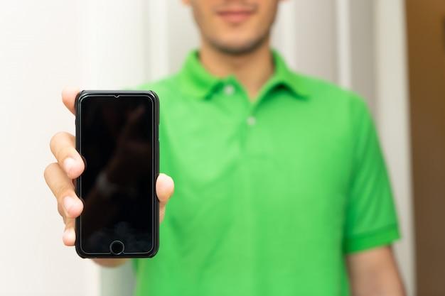 Trabalhador masculino em verde segurando a tela em branco do iphone mock up