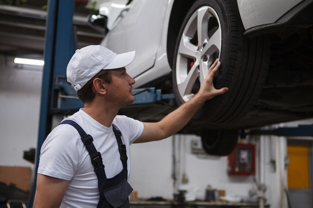 Trabalhador masculino examinando as rodas de um carro no elevador