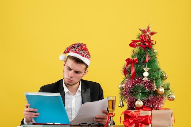 Trabalhador masculino lendo documentos ao redor da pequena árvore de natal e presentes em amarelo
