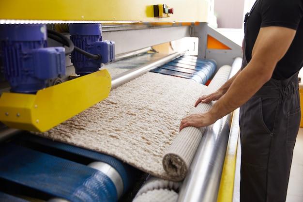 Trabalhador masculino limpando carpete em equipamento de máquina de lavar e secar roupa automática na lavanderia
