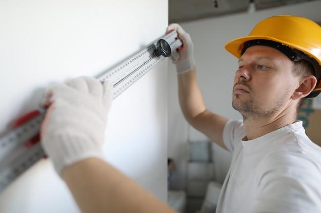 Trabalhador masculino no capacete amarelo segurar o edifício