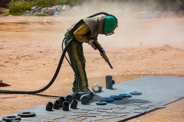 Trabalhador masculino processo de jateamento de areia, limpeza da superfície do oleoduto no aço antes de pintar na fábrica.
