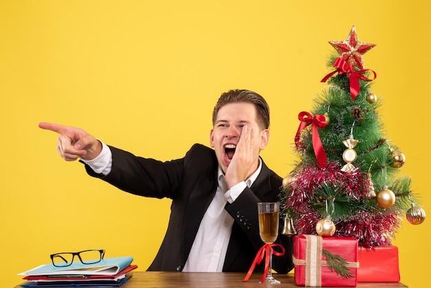 Trabalhador masculino sentado atrás de sua mesa de trabalho e chamando em voz alta Foto gratuita