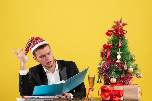 Trabalhador masculino sentado de frente e lendo documentos em amarelo
