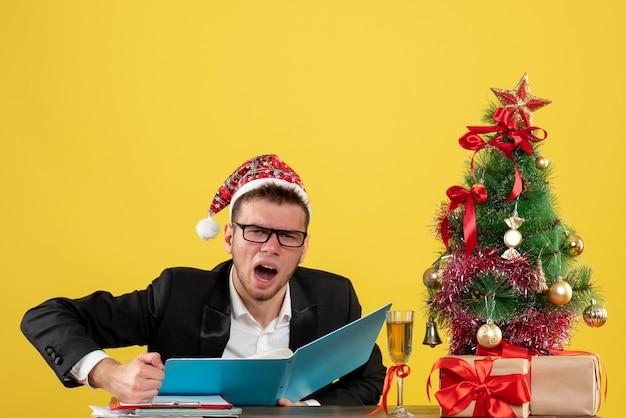 Trabalhador masculino sentado de frente, lendo documentos e gritando em amarelo