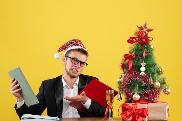 Trabalhador masculino sentado de frente segurando a nota e a calculadora em amarelo