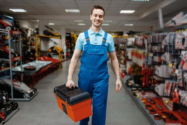 Trabalhador masculino sorridente em uniforme comprando caixa de ferramentas na loja de ferramentas
