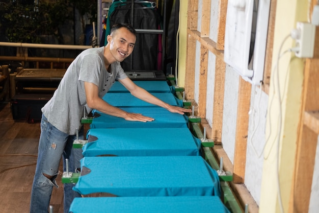 Trabalhador masculino sorrindo enquanto prepara camisetas