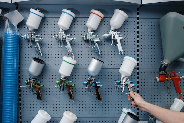 Trabalhador masculino uniformizado segura pistola de pintura pneumática na loja de ferramentas