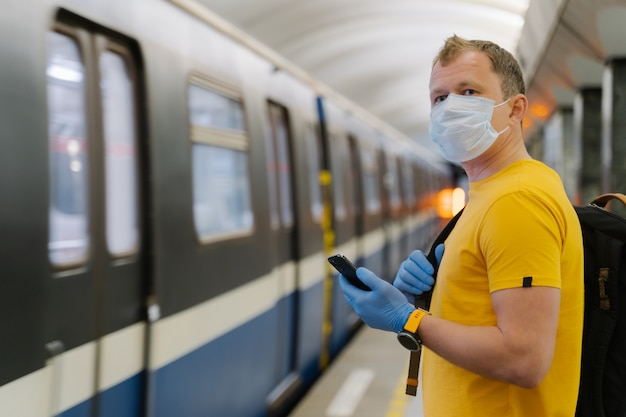 Trabalhador masculino usa smartphone moderno na plataforma, aguarda metrô ou trem, usa máscara cirúrgica para proteção contra vírus