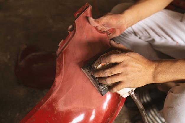 Trabalhador mecânico closeup lixar polir o corpo da motocicleta e se preparando para pintar no serviço da estação