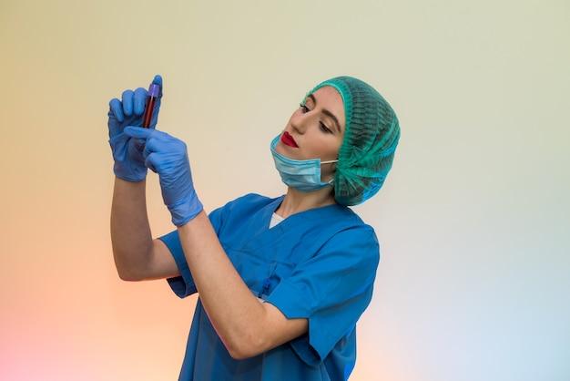 Trabalhador médico com tubos de ensaio com pose de sangue em laboratório. mulher bonita em uniforme de proteção