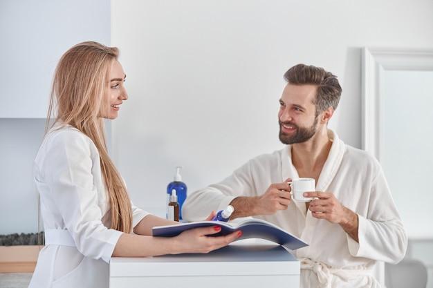 Trabalhador médico consulta brochura e tratamentos de beleza para o paciente. jovem paciente em pé perto da recepção e segurando o chá.
