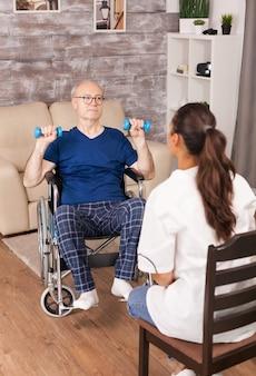 Trabalhador médico explicando os exercícios a um idoso em cadeira de rodas