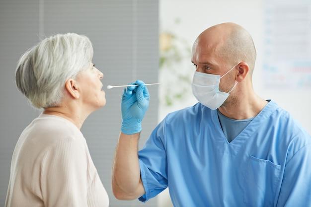 Trabalhador médico profissional testando mulher idosa fazendo cotonete na garganta