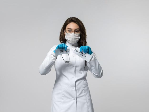 Trabalhador médico rasga papel escrito de coronavírus