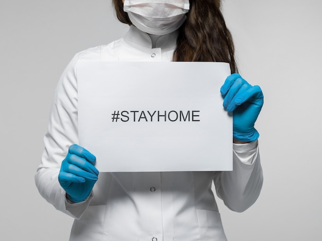 Trabalhador médico segurando o folheto com descrição stayhome
