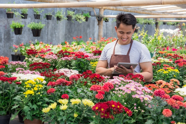 Trabalhador moderno usando tablet na loja de flores