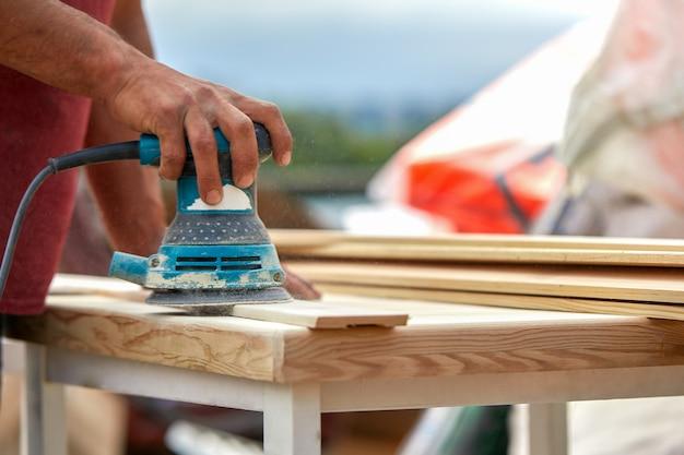 Trabalhador moedor polir uma placa de madeira. tábuas de lixar máquina excêntrica orbital.