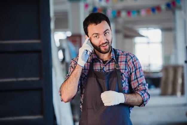 Trabalhador mostra o dedo em uma luva de pano explicando algo para alguém