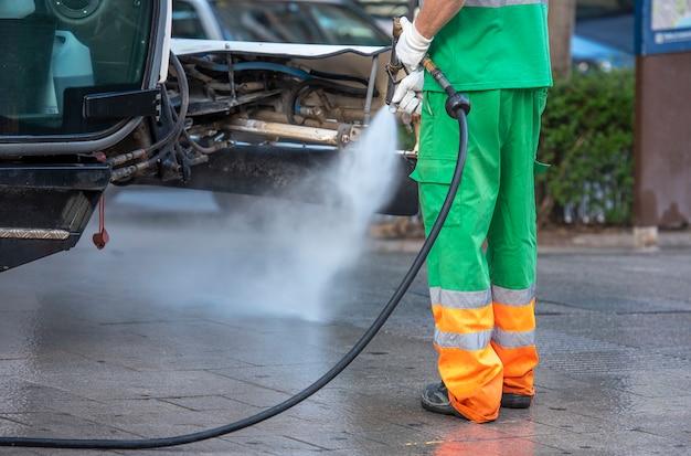 Trabalhador municipal com uma pistola de pressão de água. limpeza de ruas e mobiliário urbano, para prevenção de covid19, coronavírus