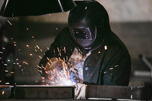Trabalhador na fábrica no capacete é de ferro no processo de soldagem faíscas brilhantes
