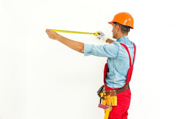 Trabalhador na medida do capacete com régua. isolado em um branco